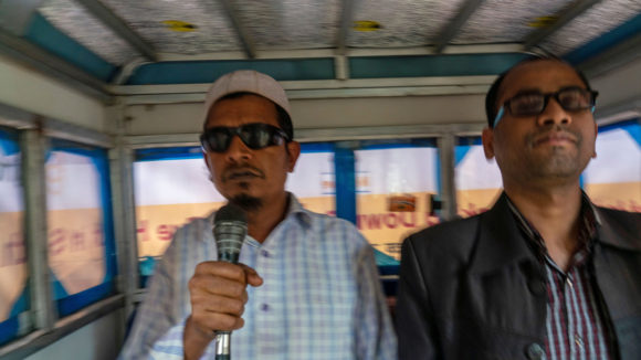 Two men announcing messages into a microphone in a tuk-tuk.