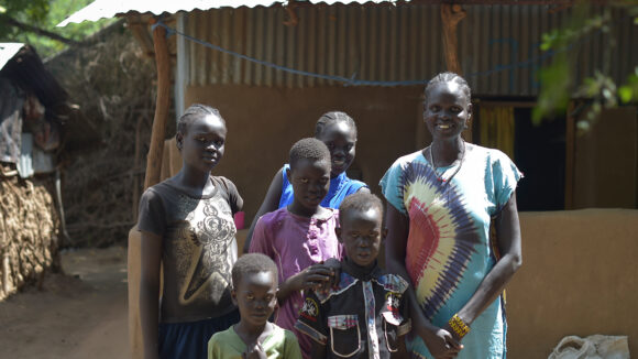 Rebecca stands alongside her five children in front of a building in Northern Kenya.