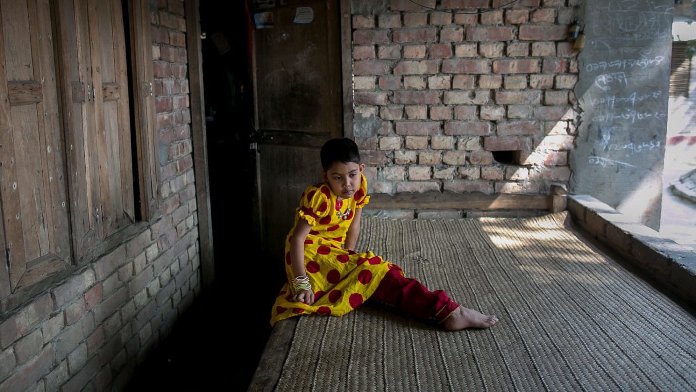 Muslima, an eight-year-old girl, sitting in the dark outside her home and looking at the floor.