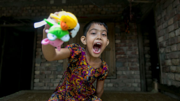 Muslima smiling gleefully with her mouth open, while playing with three colourful finger puppets.
