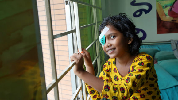 Nine-year-old Sumaiya smiling after her cataract operation at a hospital in Bangladesh.