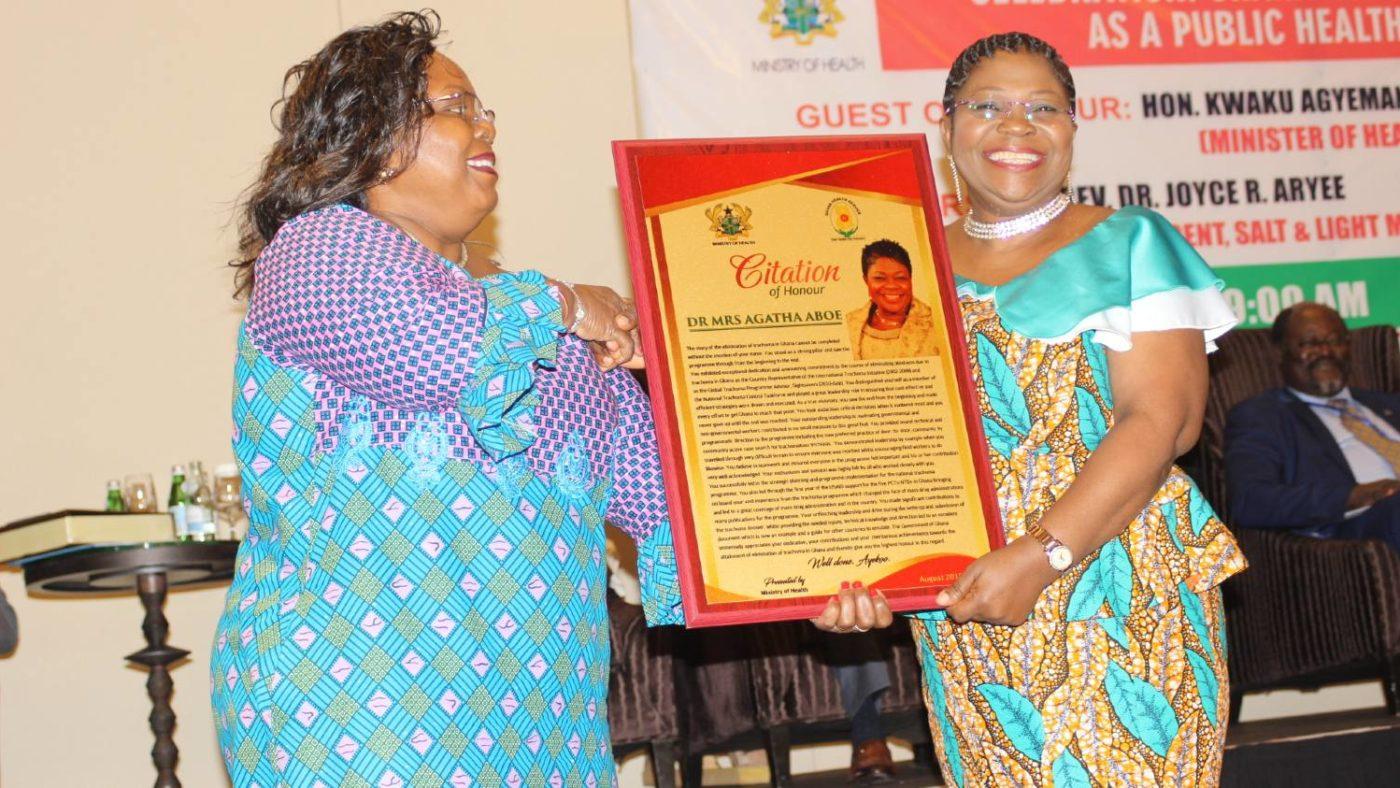 A woman receives an award.