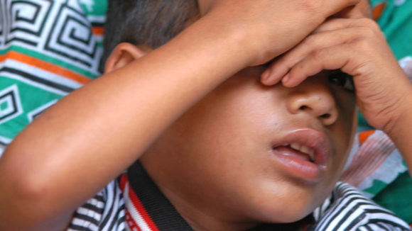 A young boy covering his eyes with his hands.