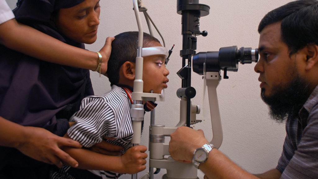 A young boy having his eyes checked by a health worker.