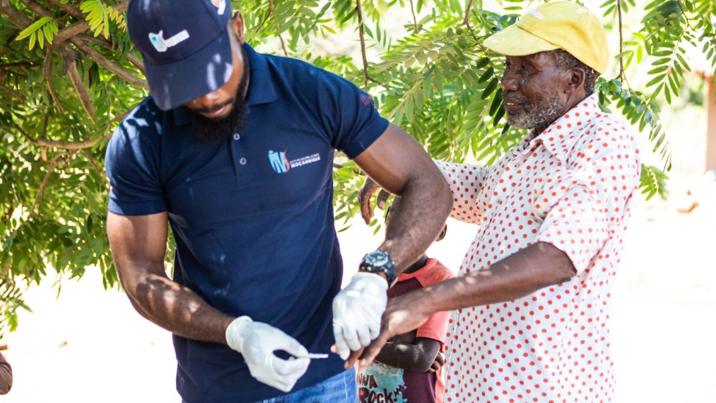 One of the survey team for the Onchocerciasis Elimination Mapping project takes a blood spot sample from a community member in Cemente, Mozambique.