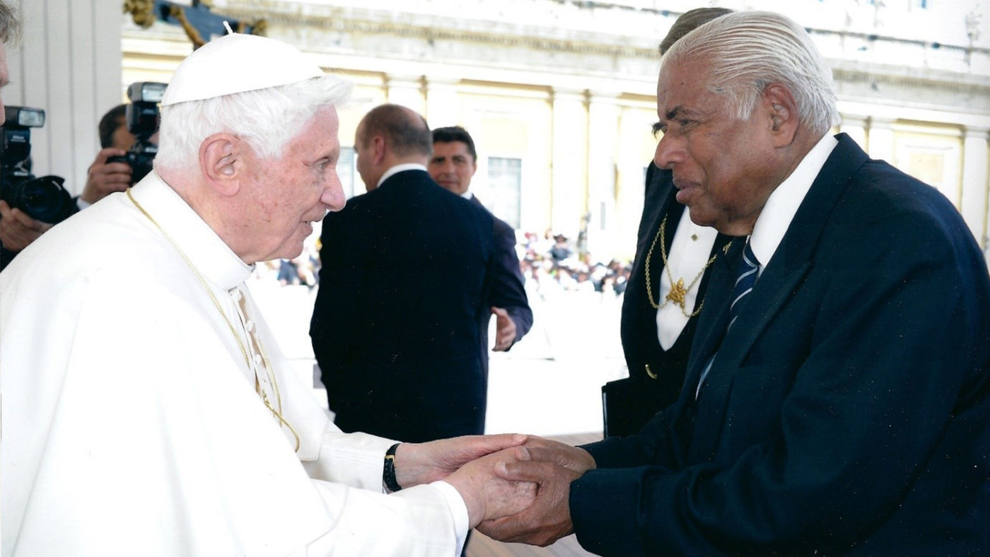 The Pope holds hands and greets another man.