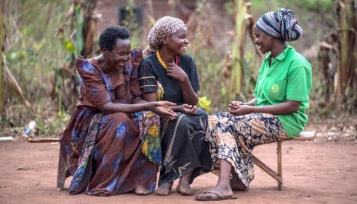 Three women communicate using sign language.