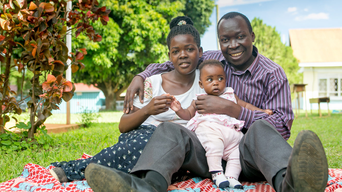 A man and women sit smiling, with their daughter in between them.