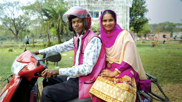 A man and women sat on a motorbike.