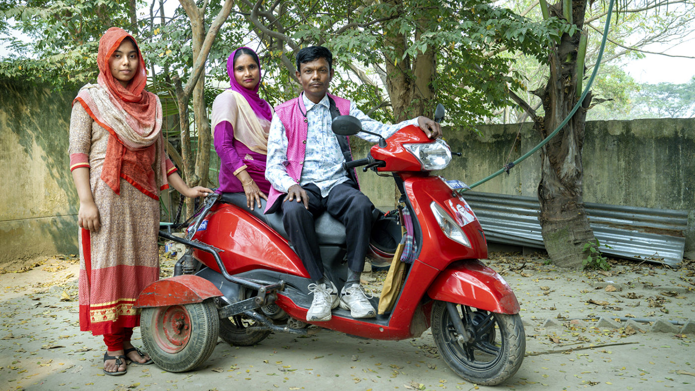 A man and wife sit on a motorbike with a young woman standing beside them.