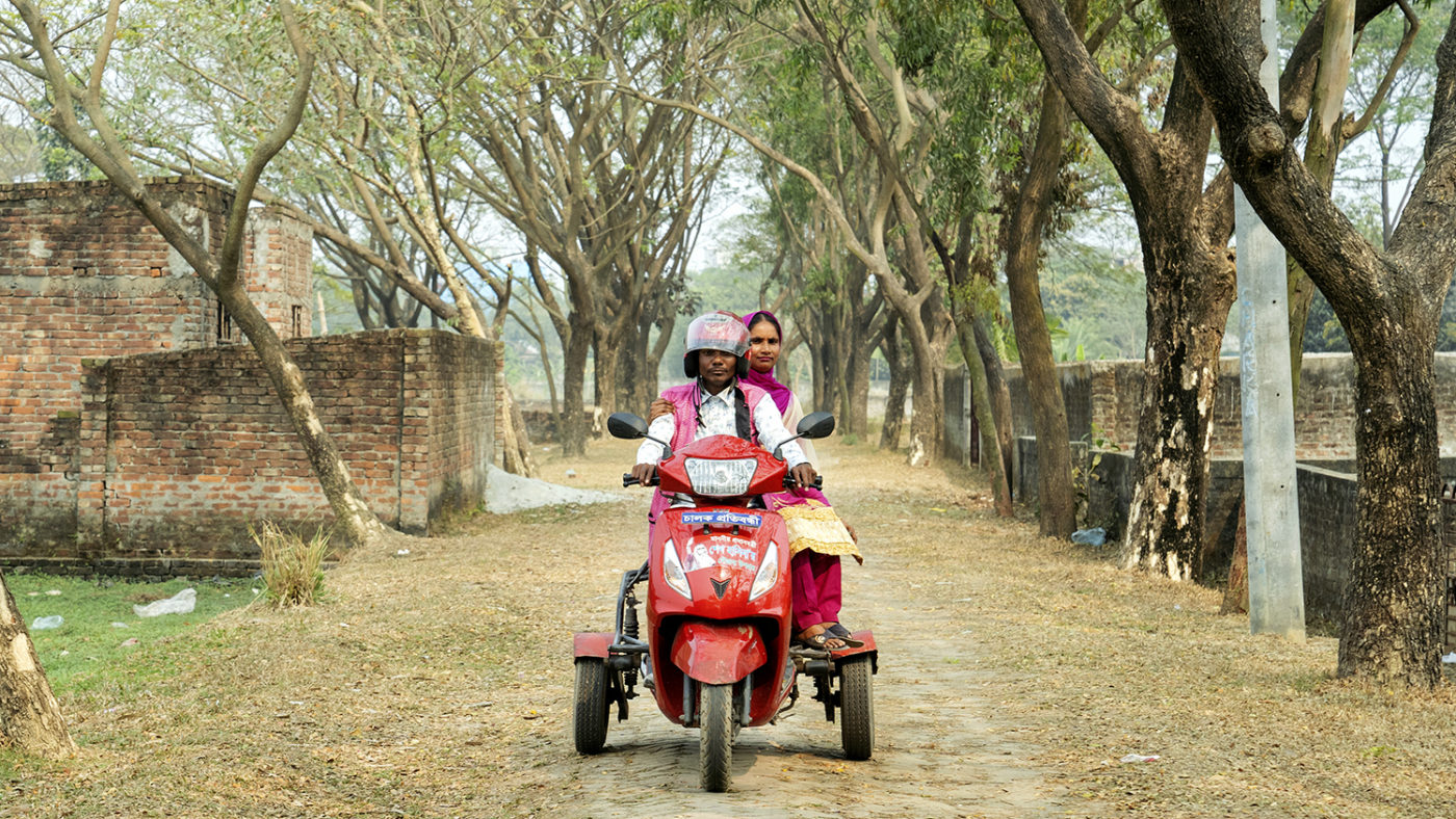 A man and woman riding a motorbike along a rural road.