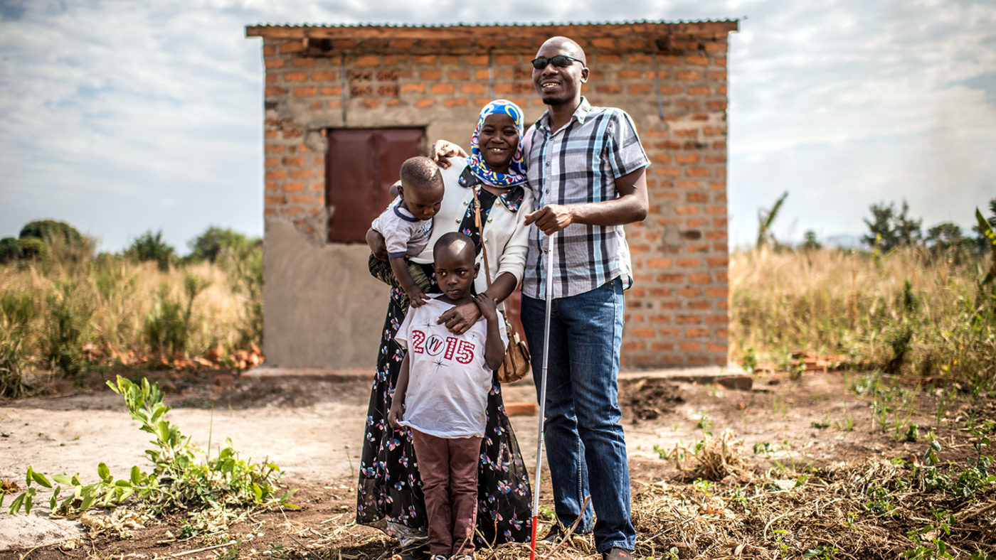 Husband and wife, with two children, stand outside their home.
