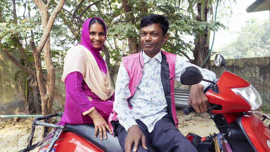 A man and wife sit on a motorbike.