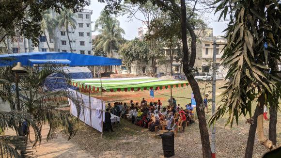 An outdoor meeting in a grass courtyard.