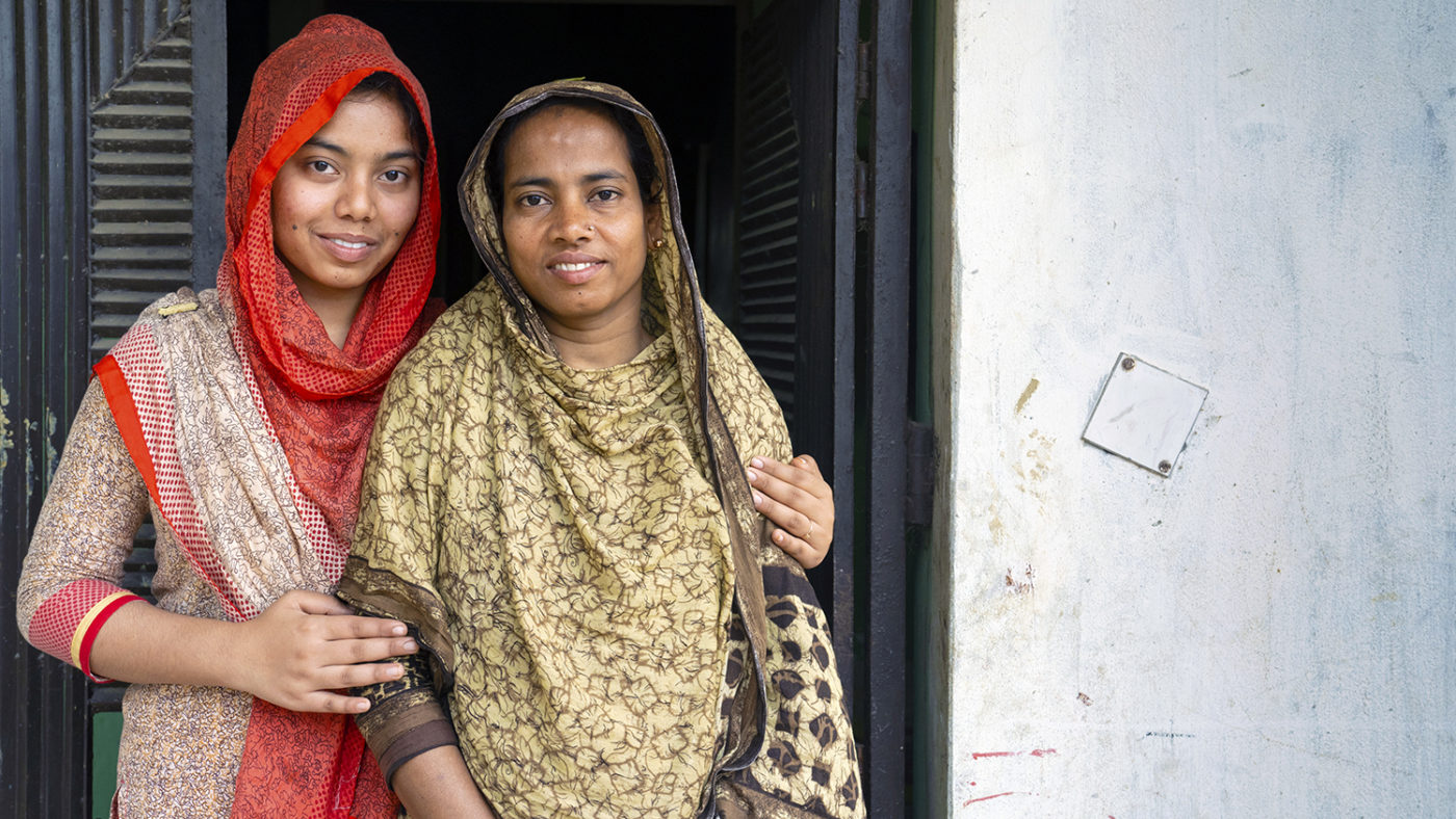 A teenager and her mother stand together smiling.