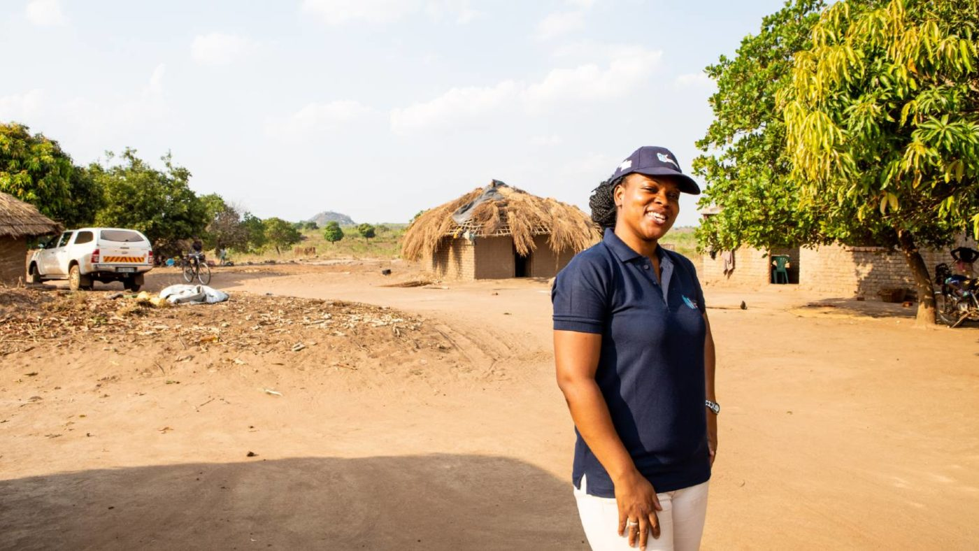 A woman stands for a portrait outside after completing surveys for river blindness in Mozambique.