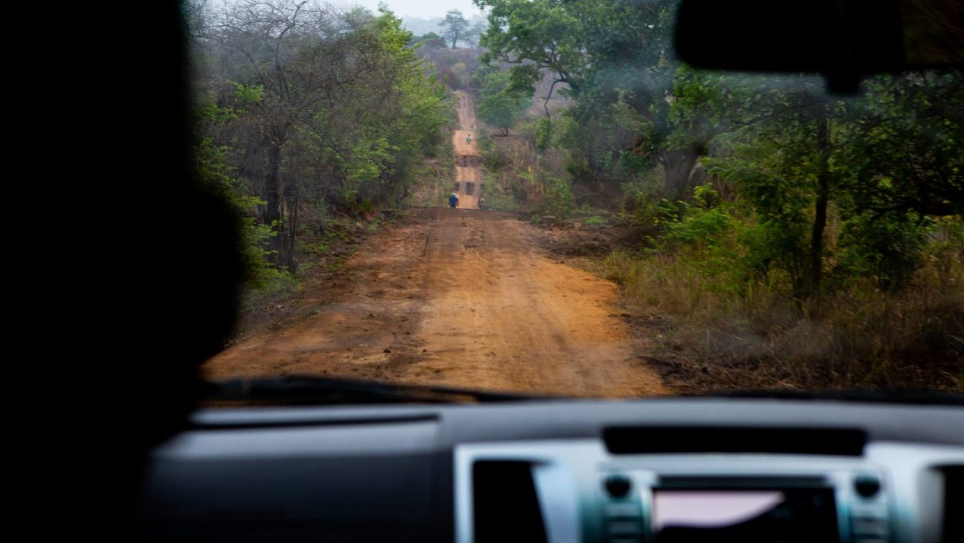A bumpy dirt road in Zambezia Province as seen through the front window of a car