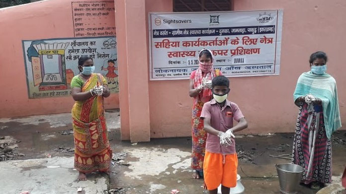 A group of four people stand outside wearing protective masks and washing their hands.