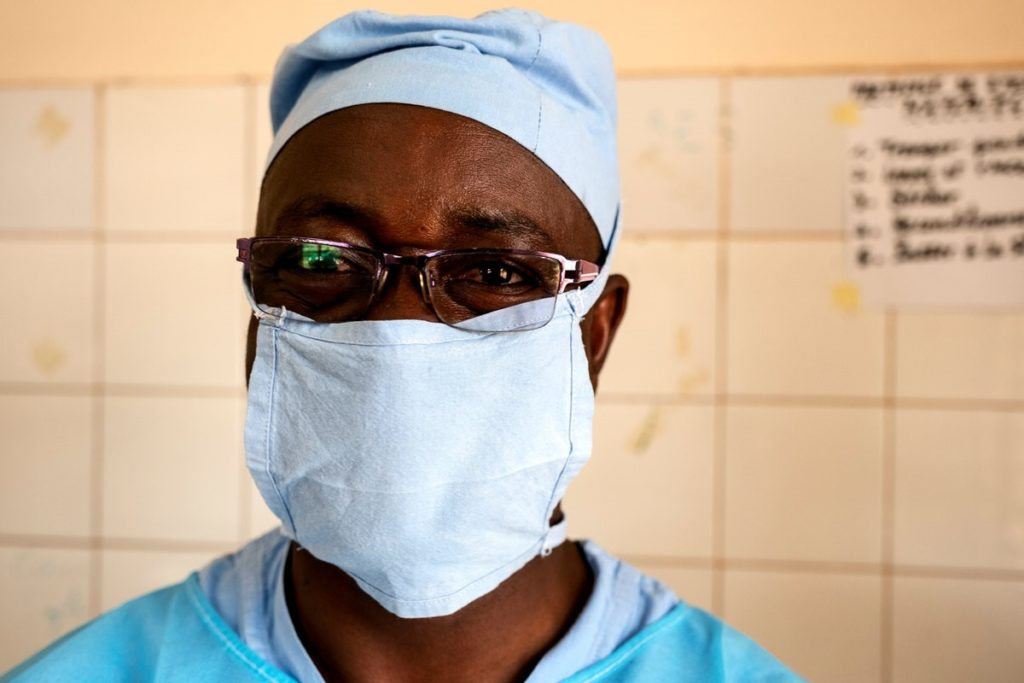 Dr Amadou wearing scrubs and a face mask.
