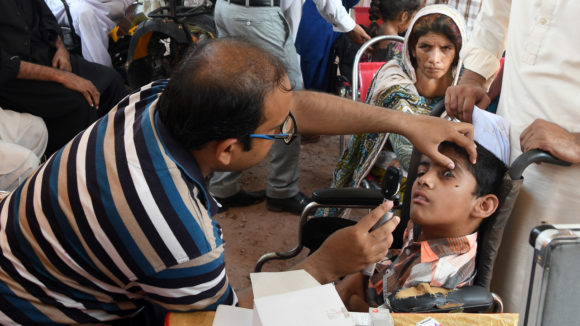 A man examines the eyesight of a young boy who uses a wheelchair.