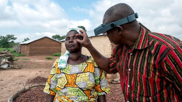 A male ophthalmologist checks a woman's eyes for signs of trachoma.