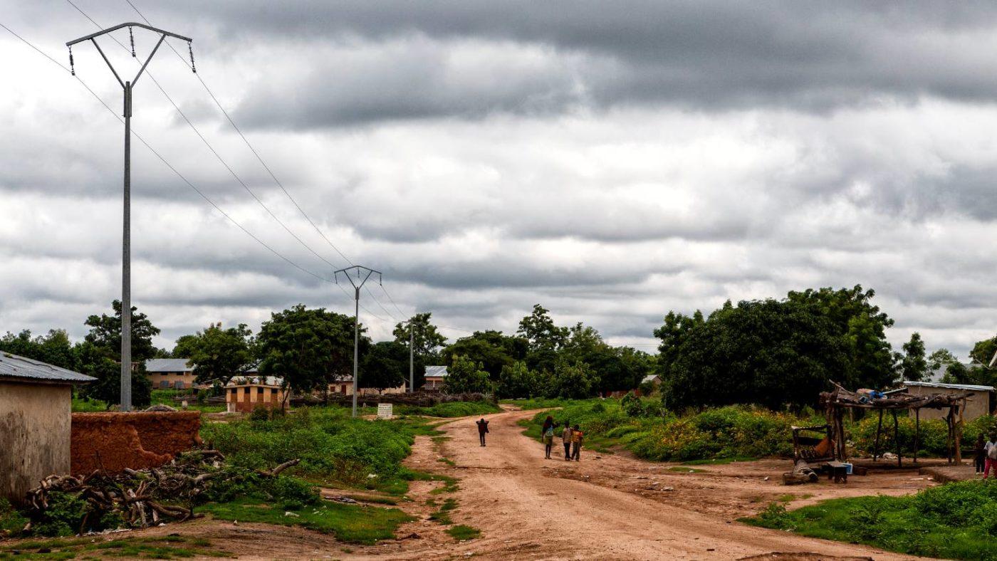 Community members walk down a long dirt road in rural Benin.