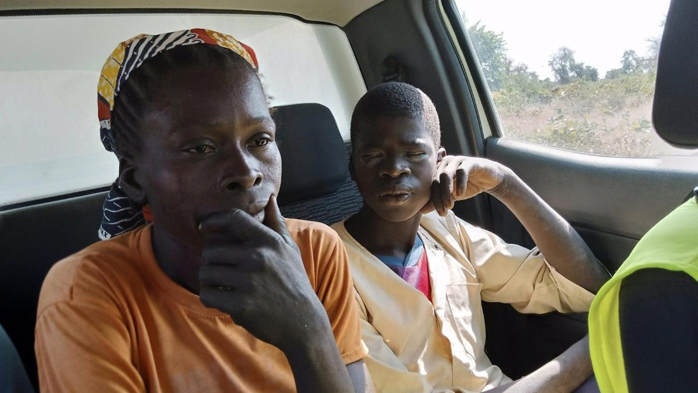 Boy with trichiasis with his mother in a car, travelling to hospital.