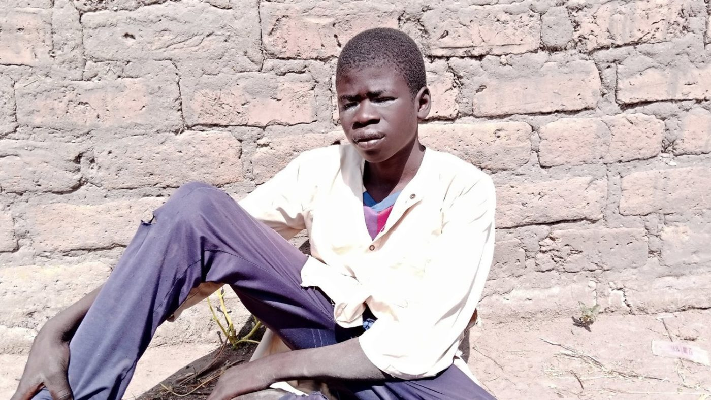 a boy sits next to a wall. his eyes are watery and sore.