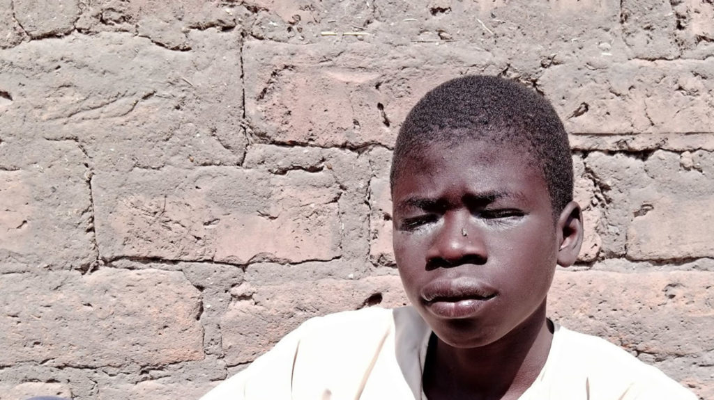 Teenage boy with trichiasis, sitting by a wall.