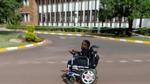 A young man using a wheelchair on a road in Kenya.