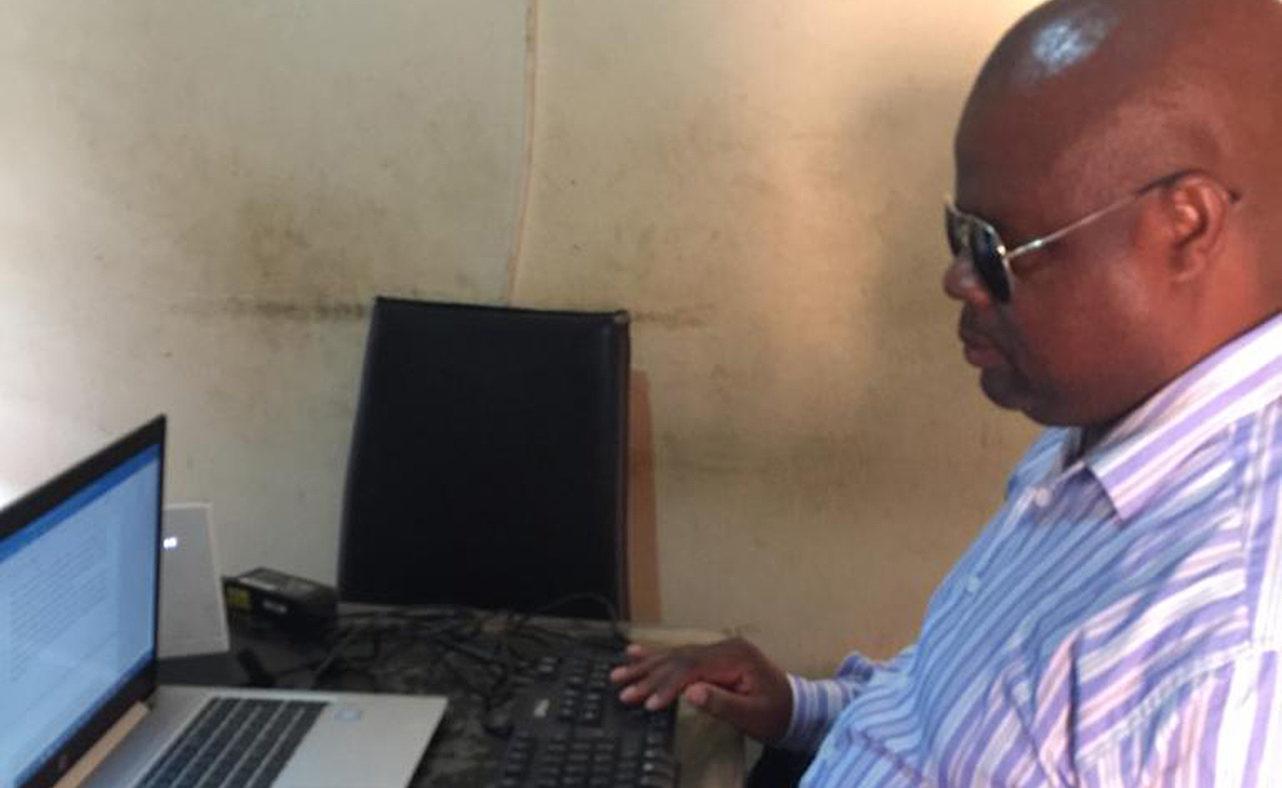 Thomas Mtonga sitting at his laptop.