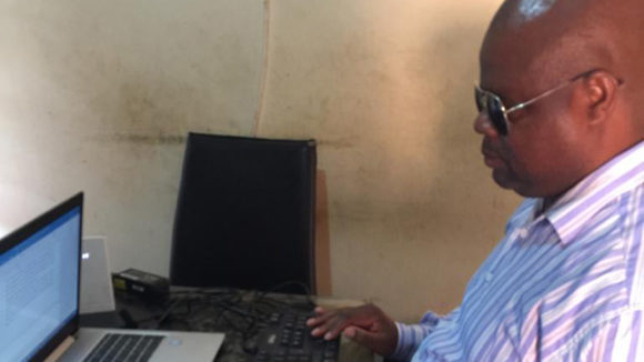 Thomas Mtonga sitting at his laptop.