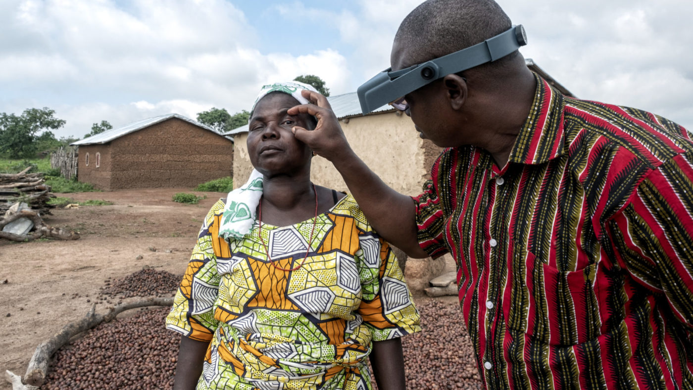 A woman has her eyes checked by a doctor.
