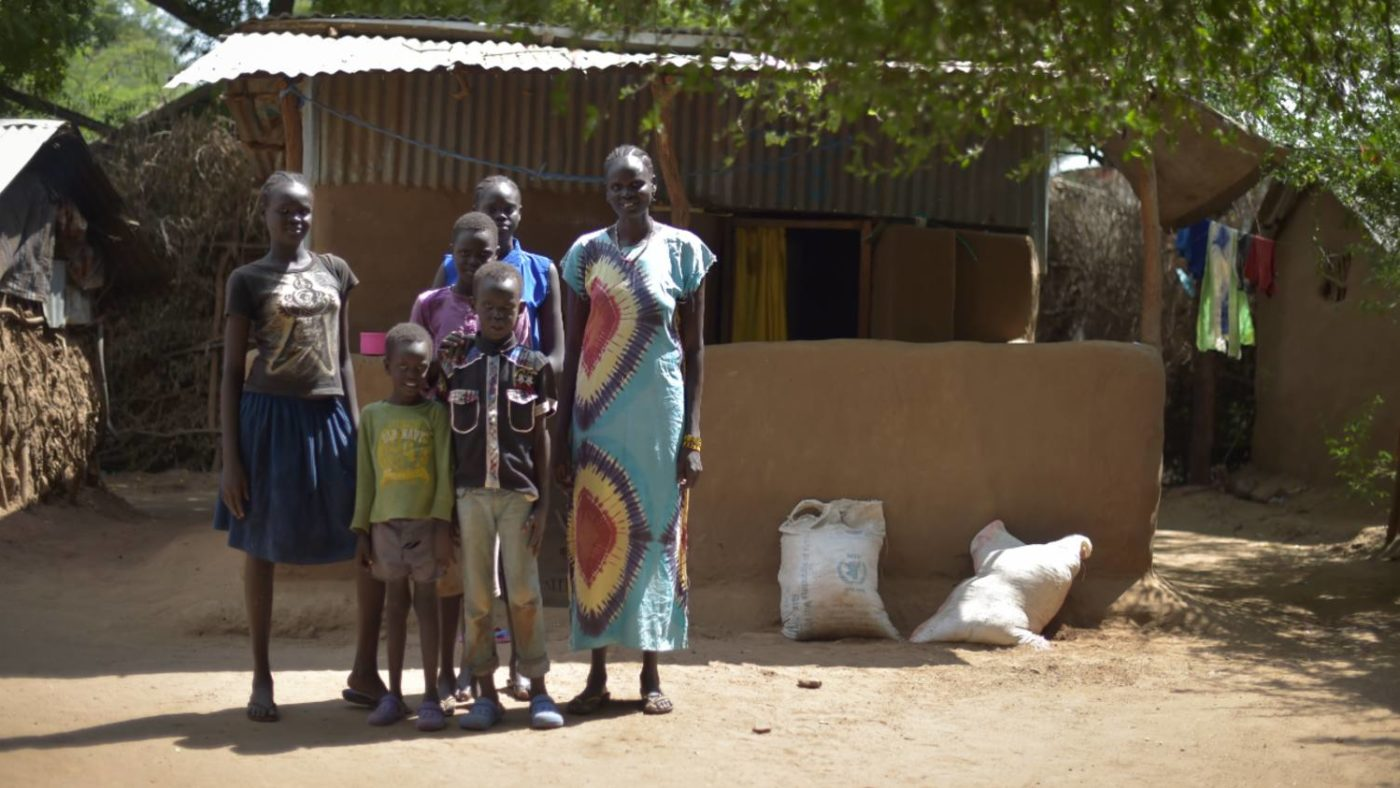 Rebecca stands with her family outside her home, or refugee accommodation in Kenya.