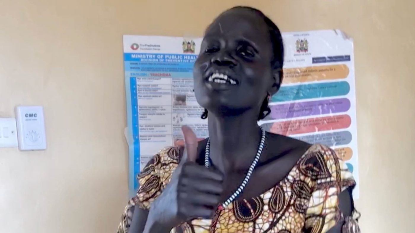 A woman smiles and gives a thumbs up.