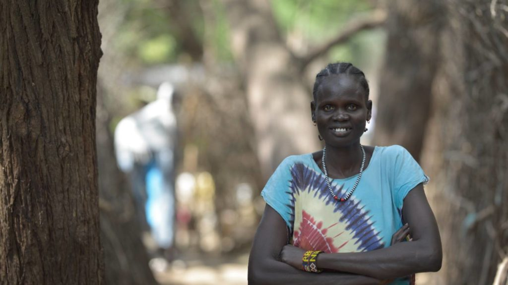 Rebecca stands with her arms folded outside her accommodation in the Kenyan refugee camp