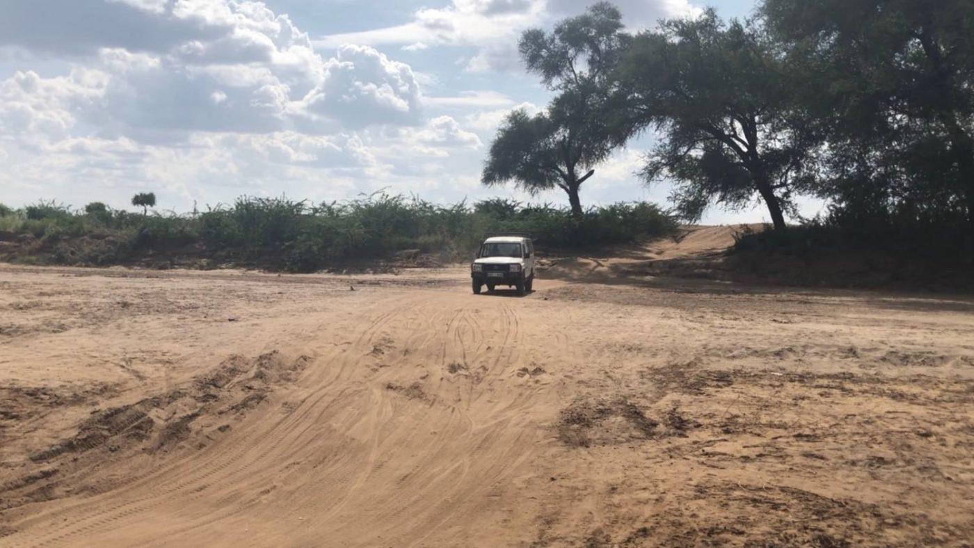 A car travels along a dirt road.