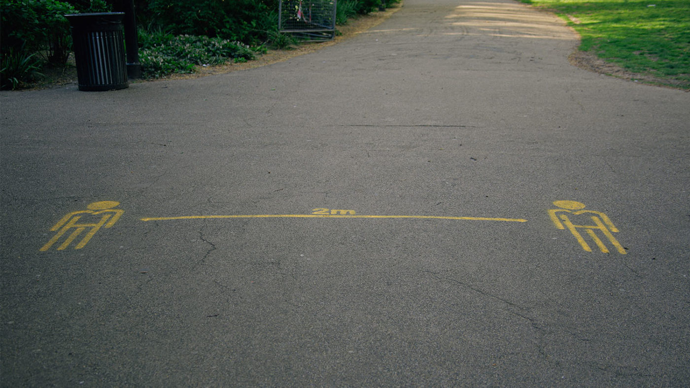 A floor marking on a concrete path showing a two-metre gap.