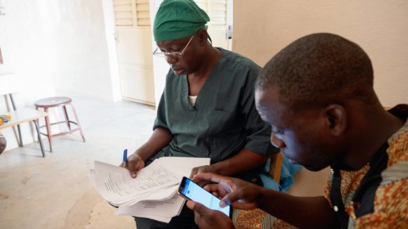 An assistant use a mobile app to input trachoma patient data from the surgeon.