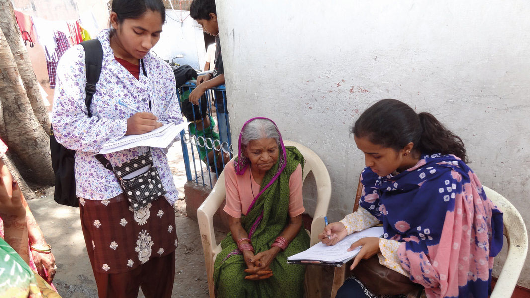 Two young women holding clipboards make notes with a pen, and are shown next to an elderly woman who is seated outside in Bhopal, India.