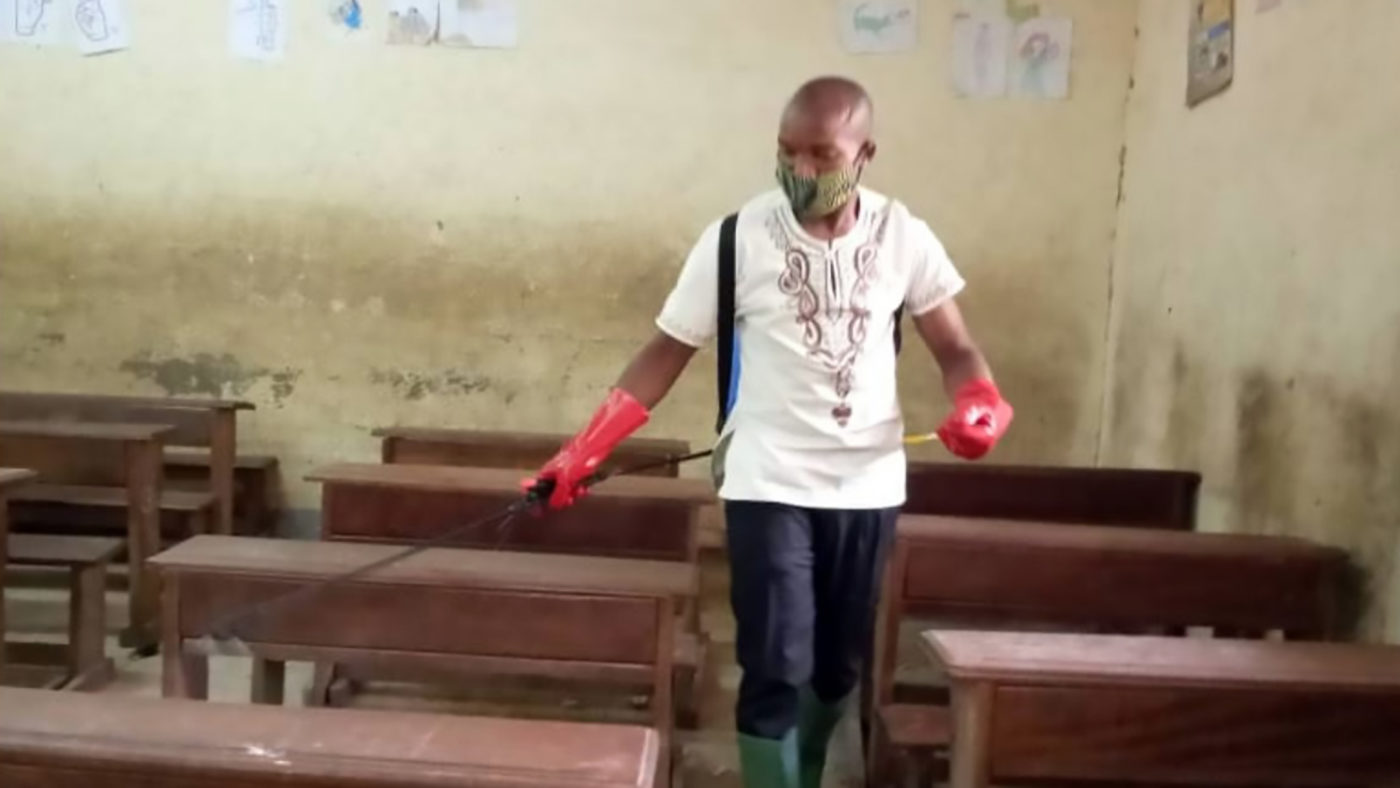 A man wearing a face mask and gloves sprays disinfectant in a classroom.