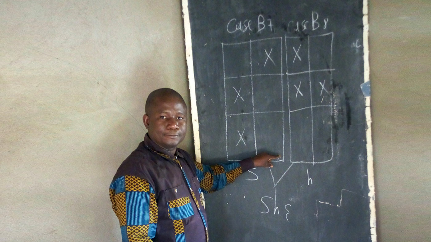 A man pointing to a blackboard.