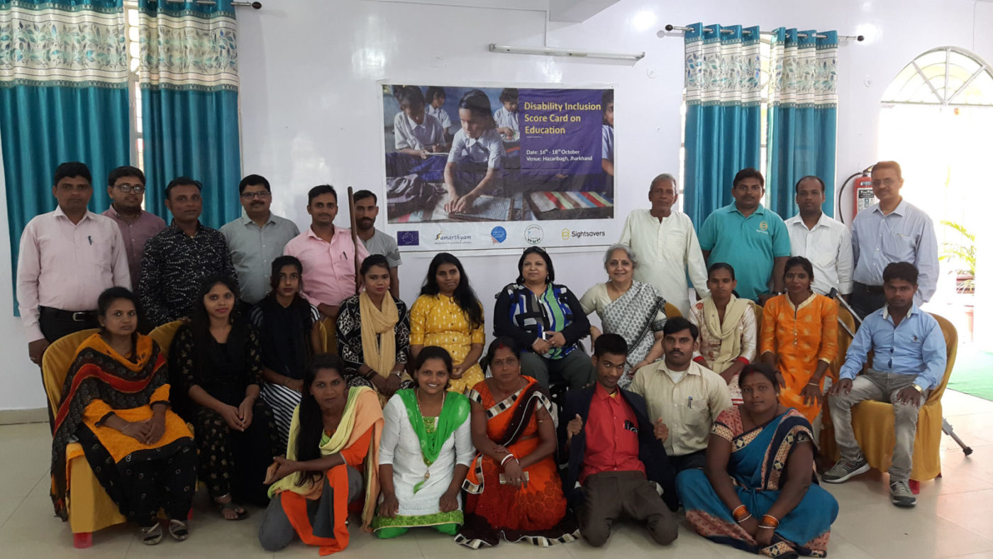 A large group of about 25 people with disabilities in an office setting posing for a photo.