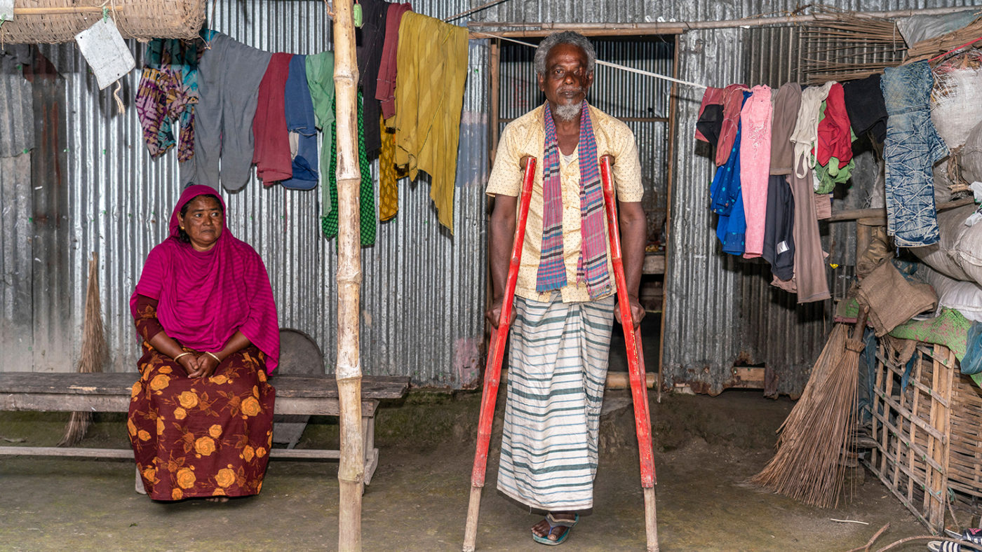 A woman sitting and a man using crutches to stand.