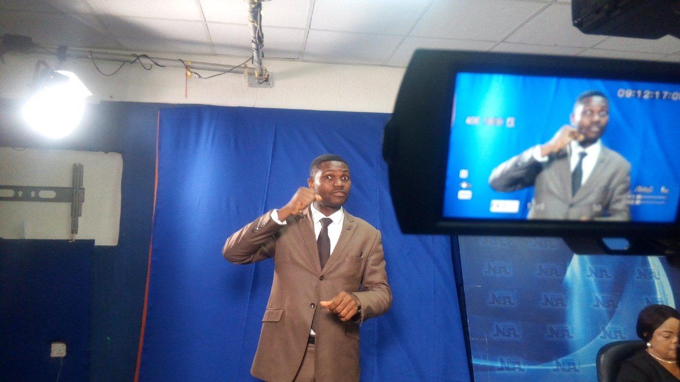 A sign language interpreter in a TV studio.
