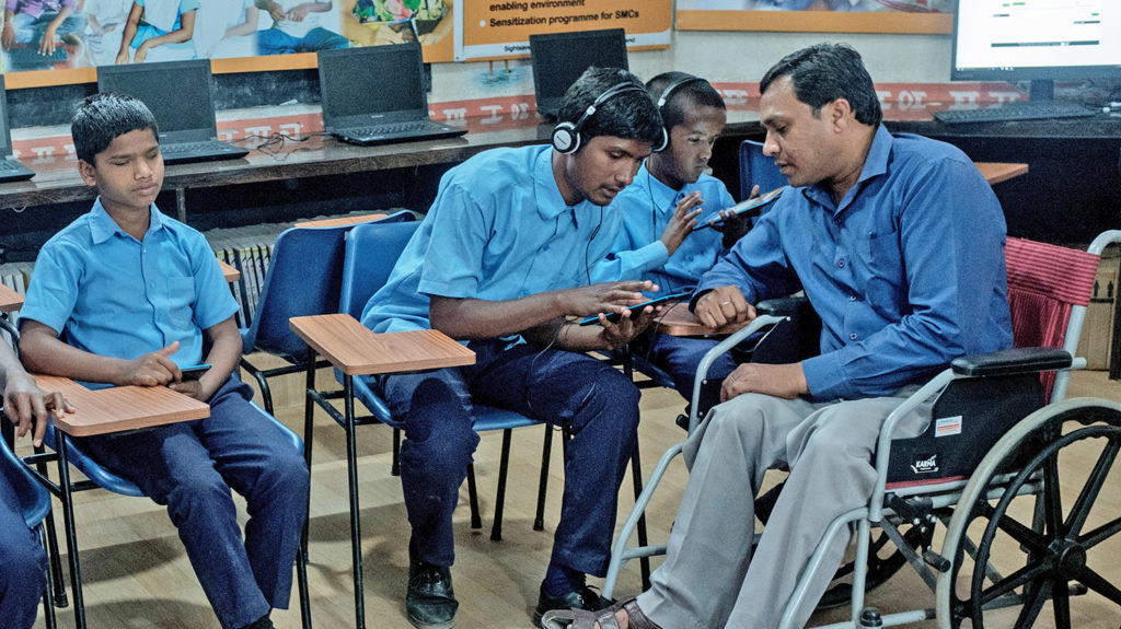 Three male students use small assistive devices in a classroom with the help of a teacher who uses a wheelchair.