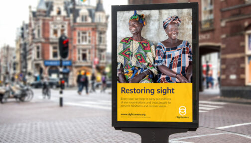 A Sightsavers branded poster displayed on a busy street.