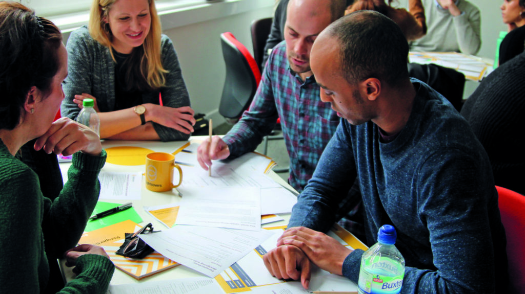 A group of Sightsavers employees around a desk working on a project.