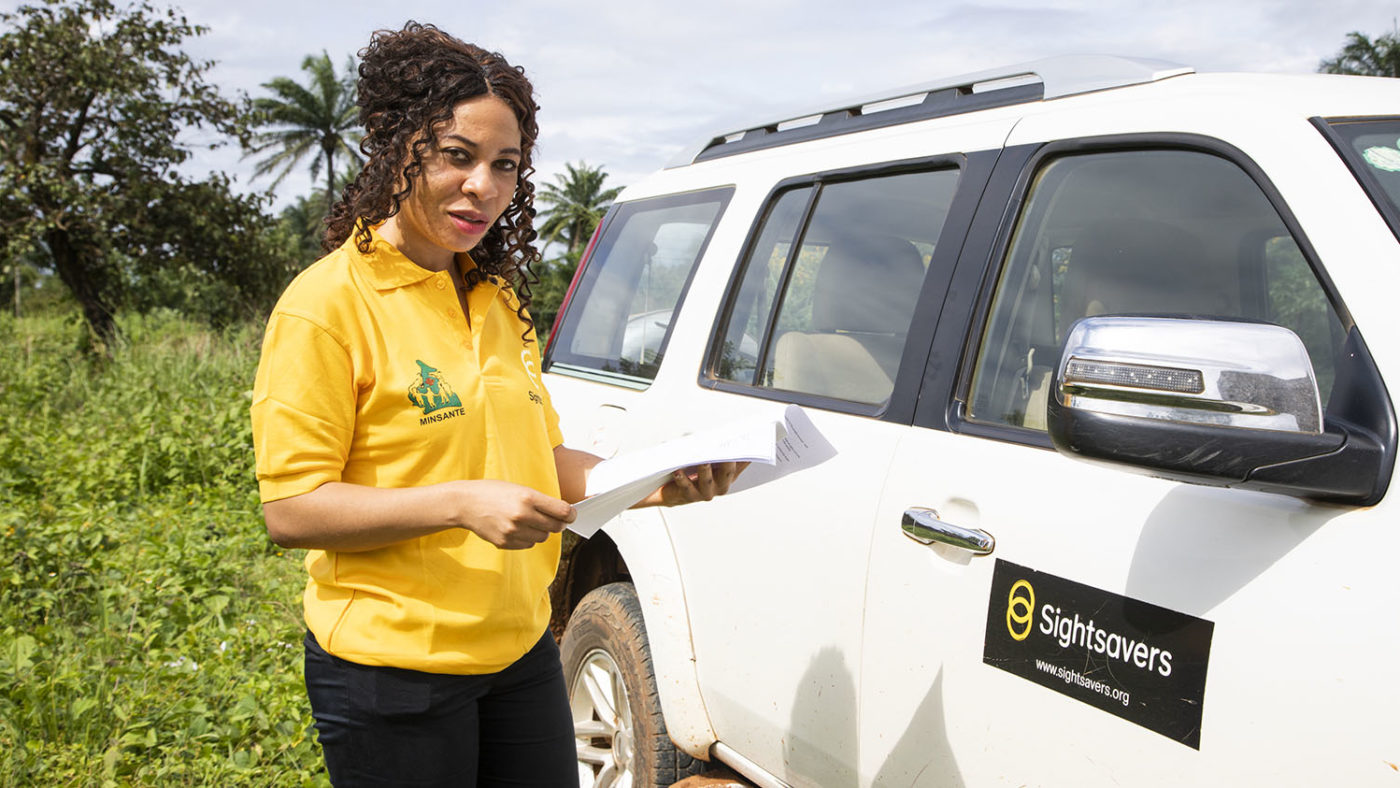 Kareen is shown in a Sightsavers top standing outside next to a Sightsavers vehicle.