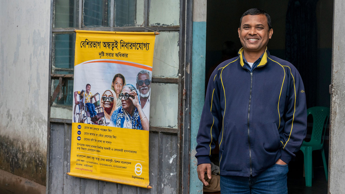 A man standing smiling, next to a Sightsavers' sign in Bangla.